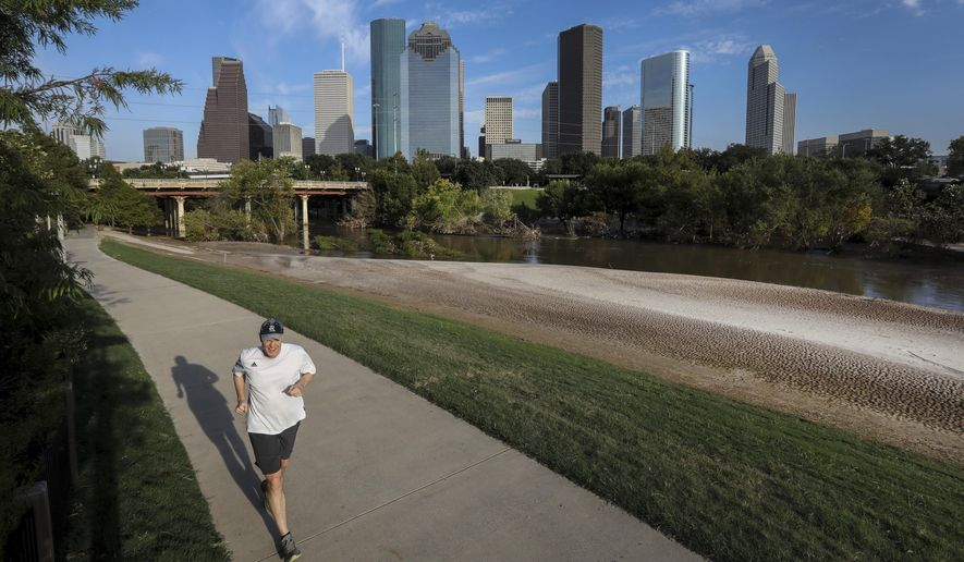 A jogger runs along a trail at Buffalo Bayou Park, Tuesday, Sept. 12, 2017, in Houston. Runners and bikers returning to the park in the wake of Hurricane Harvey are finding a vastly different landscape, more desert than prairie, blanketed with untold tons of sandy sediment.   (Jon Shapley/Houston Chronicle via AP)