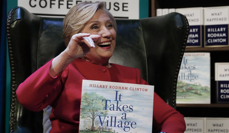 "Hillary Clinton holds her book ""It Takes A Village"" as she sits on stage at the Warner Theatre in Washington, Monday, Sept. 18, 2017, during a book tour event for her new book ""What Happened"" hosted by the Politics and Prose Bookstore. (AP Photo/Carolyn Kaster)"