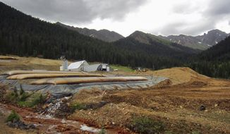 This July 27, 2017, photo shows a U.S. Environmental Protection Agency wastewater treatment plant in the San Juan Mountains outside Silverton, Colo. The plant treats water flowing from the Gold King Mine, where the EPA inadvertently triggered a spill of 3 million gallons of wastewater in 2015. The EPA is installing a barrier and valve inside the mine to regulate the flow of wastewater.(AP Photo/Dan Elliot)