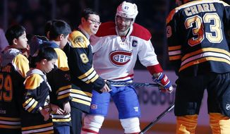 FILE - In this Feb. 12, 2017, file photo, ORG Packaging Chairman Zhou Yunjie (8) prepares for the ceremonial puck drop with Boston Bruins' Zdeno Chara (33), of Slovakia, and Montreal Canadiens' Max Pacioretty (67) before an NHL hockey game in Boston. The NHL is making a major push in China beginning with its first two preseason games between the Vancouver and Los Angeles Kings in Shanghai and Beijing this week. The NHL also has an influential partner on the ground in Zhou Yunjie, the billionaire founder of a Chinese drinks packaging company who has devoted significant time and resources to building the game he fell in love with as a youth in Beijing. (AP Photo/Michael Dwyer, File)