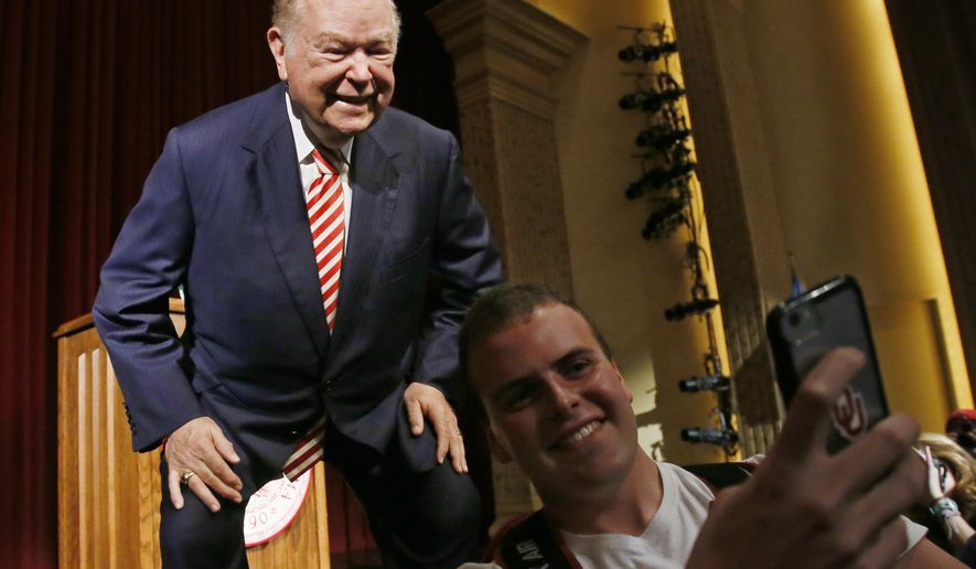 University of Oklahoma President David Boren, a former Democratic governor and U.S. Senator, poses for a selfie with a student following his announcement that he will resign as head of the state's flagship university at the end of the current school year, at a news conference in Norman, Okla., Wednesday, Sept. 20, 2017. (AP Photo/Sue Ogrocki)