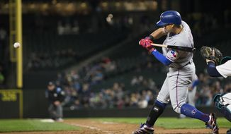 Texas Rangers' Shin-Soo Choo hits a sac fly off of Seattle Mariners pitcher Nick Vincent to score Texas Rangers' Will Middlebrooks in the eighth inning of a baseball game Tuesday, Sept. 19, 2017, in Seattle. (AP Photo/Lindsey Wasson)