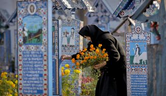 An elderly woman holds flowers, walking between painted crosses in the Merry Cemetery, in Sapanta, northwestern Romania, Sunday, Sept. 10, 2017. The Merry Cemetery is a collection of more than 1,000 vivid Orthodox crosses decorated with colorful epitaphs and childlike drawings. (AP Photo/Vadim Ghirda)
