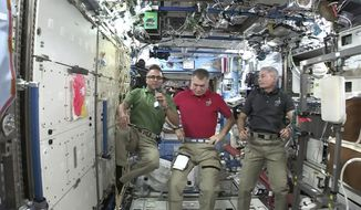 Joe Acaba, left, the first astronaut of Puerto Rican heritage, talks during an interview with The Associated Press alongside Italy's Paolo Nespoli, center, and Mark Vande Hei from the International Space Station on Wednesday, Sept. 20, 2017. Acaba offered words of comfort to Puerto Ricans enduring the wrath of Hurricane Maria. (NASA via AP)