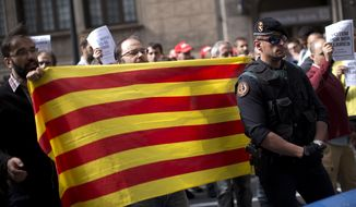 Pro-independence demonstrators protest outside the headquarters of the region's department of External Affairs in Barcelona, Spain, Wednesday, Sept. 20, 2017. Spanish police arrested 12 people Wednesday in raids on offices of the regional government of Catalonia, news reports said, intensifying a crackdown on the region's preparations for a secession vote that Spain says is illegal. (AP Photo/Emilio Morenatti)