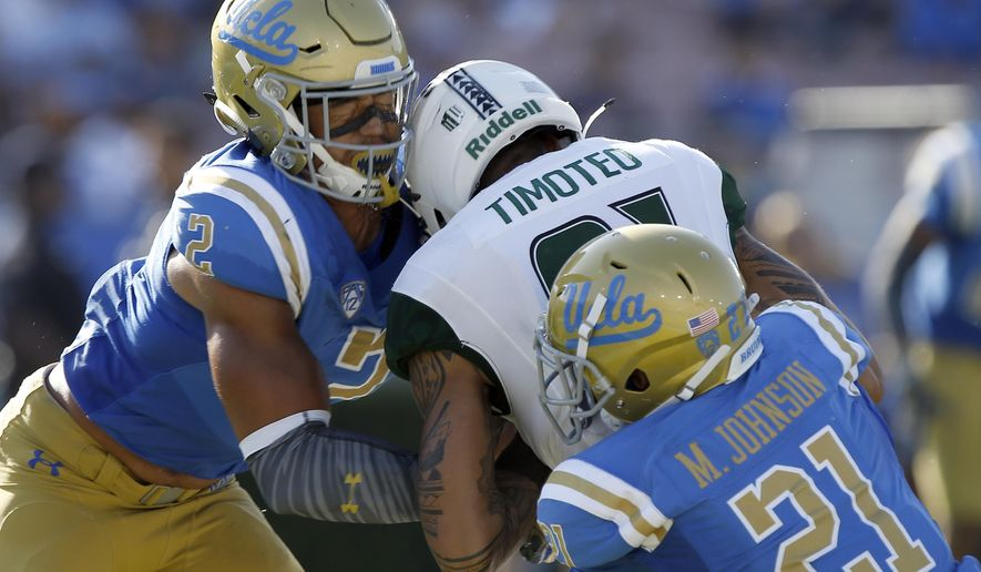 FILE - In this Sept. 9, 2017, file photo, Hawaii wide receiver Kalakaua Timoteo, center, drops the ball and gets leveled by UCLA linebacker Josh Woods, left, and hit from behind by defensive back Mossi Johnson (21), during the second half of an NCAA college football game in Pasadena, Calif. Woods was penalized for targeting and ejected. College football's Bowl Subdivision has seen a 73-percent increase in the number of targeting penalties enforced through the first three weeks of the season compared with the same point in 2016.(AP Photo/Alex Gallardo, File)