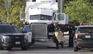 FILE- In this July 23, 2017, file photo, San Antonio police officers investigate the scene where several people were found dead in a semitrailer loaded with over a dozen others outside a Walmart store in San Antonio. Authorities say James Bradley Jr., the driver of the semitrailer, faces additional charges in the smuggling case and another defendant has now been charged. The U.S. attorney's office in San Antonio says a grand jury returned the superseding indictment Wednesday. Sept. 20. (AP Photo/Eric Gay, File)