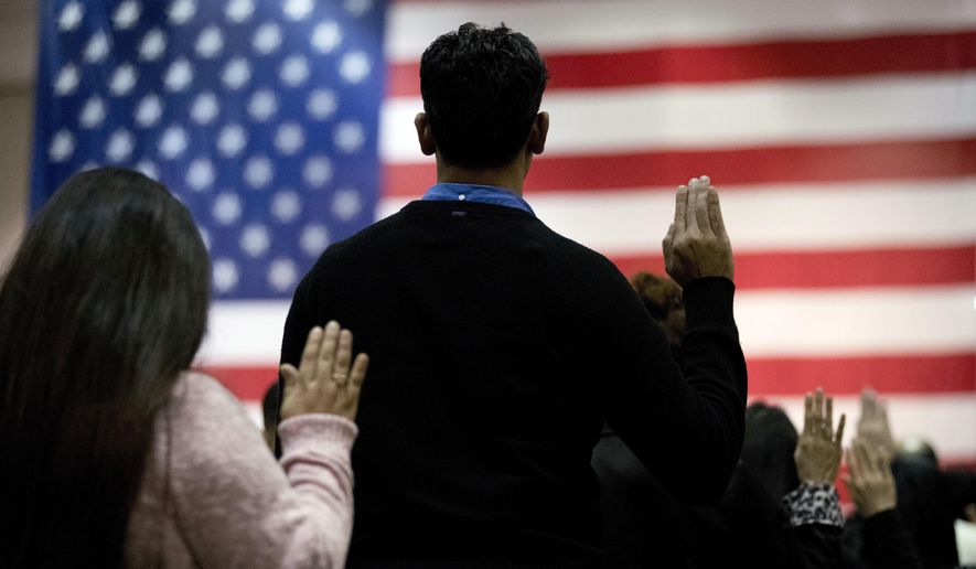 "FILE - In this Feb. 15, 2017 file photo, people take the oath of citizenship during a naturalization ceremony at the Los Angeles Convention Center. In a Los Angeles ceremony Wednesday, Sept. 20, 2017, more than 9,000 new American citizens will hear a newly recorded message from President Donald Trump welcoming them to the country and urging them to help others assimilate to help keep the country ""safe, strong and free."" It is the first time the message from Trump will be played at the massive swearing-in ceremonies held each month in Southern California. (AP Photo/Jae C. Hong, File)"