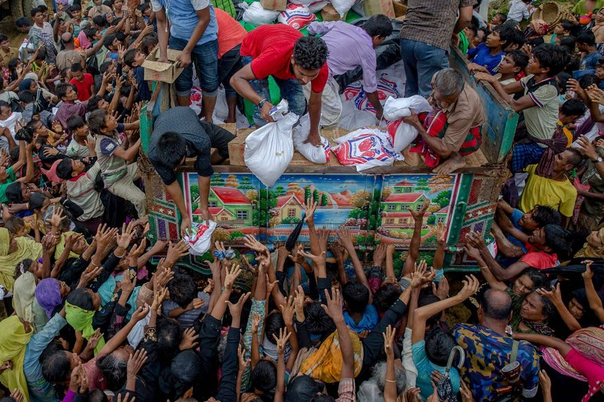 Royhingya refugees from Myanmar receiving food from Bangladeshi aid workers          Associated Press photo