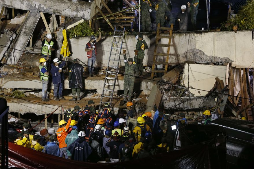 Rescue personnel work on the rescue of a trapped child at the collapsed Enrique Rebsamen primary schoool in Mexico City, Sept. 20, 2017.  A wing of the school collapsed after a powerful earthquake jolted central Mexico on Tuesday, killing scores of children and trapping others. (AP Photo/Marco Ugarte)