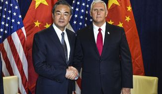 In this photo released by China's Xinhua News Agency, Chinese Foreign Minister Wang Yi, left, shakes hands as he poses for a photo with Vice President Mike Pence during a meeting at the United Nations headquarters in New York, Wednesday, Sept. 20, 2017. (Li Rui/Xinhua via AP)