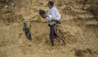 """Alishaan, a Rohingya Muslim man, carries his sick mother Aishya Khatoon to a hospital at Taiy Khali refugee camp, Bangladesh, Thursday, Sept. 21, 2017. More than 400,000 Rohingya Muslims have fled to Bangladesh since Aug. 25, when deadly attacks by a Rohingya insurgent group on police posts prompted Myanmar's military to launch """"clearance operations"""" in Rakhine state. (AP Photo/Dar Yasin)"""