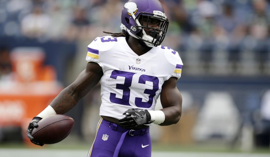 FILE - In this Aug. 18, 2017, file photo, Minnesota Vikings running back Dalvin Cook holds the ball before an NFL football preseason game against the Seattle Seahawks in Seattle. The Vikings host the Tampa Bay Buccaneers on Sunday.(AP Photo/Scott Eklund, File)