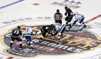 Players of the Los Angeles Kings, and the Vancouver Canucks fight for the puck during the NHL China preseason hockey game at Mercedes-Benz Arena in Shanghai, China, Thursday, Sept. 21 , 2017. (AP Photo)