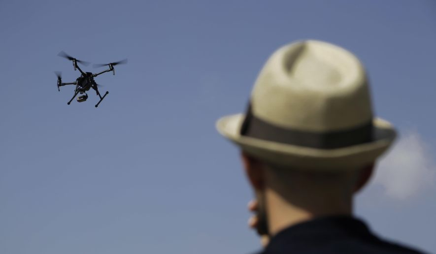 A man watches a drone during a demonstration at the British police station inside the British military base in Dhekelia in southeast of the island of Cyprus, Thursday, Sept. 21, 2017. (AP Photo/Petros Karadjias)