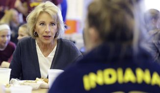 In this Sept. 15, 2017 photo, U.S. Secretary of Education Betsy DeVos talks with Gracie Johnson during a hog roast before a high school football game between Eastern Hancock and Knightstown in Charlottesville, Ind. DeVos uses a private jet to fly around the country to tour schools and attend other work events, the Associated Press has learned.  (AP Photo/Darron Cummings)