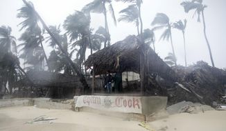 A person looks out from the Captain Cook restaurant damaged during the crossing of Hurricane Maria, on Cofrecito Beach, in Bavaro, Dominican Republic, Thursday, Sept. 21, 2017.  Rain from the storm will continue in the Dominican Republic for the next two days according to meteorologists.(AP Photo/Tatiana Fernandez)