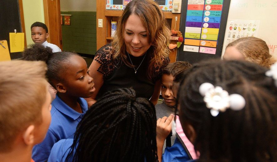 In this Sept. 11, 2017, photo, Mother Teresa Academy Principal Jamie Brim talks with second graders in Erie, Pa. (Jack Hanrahan/Erie Times-News via AP)