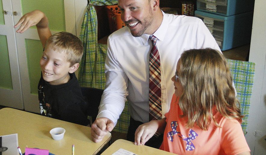 In this Aug. 22, 2017 photo, Principal Ryan Scott shares a laugh with third graders Charlie  Russell and Kaya Forlines while visiting classrooms at Main Street Elementary School in Shelbyville, Ill. The new principal at Main Street says his plan is to be as visible and accessible as possible, building relationships among the school, families and community. (Jim Bowling/Herald & Review via AP)