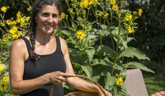 In this Aug. 9, 2017 photo, Tina Hope is seen harvesting basket full of calendula flower tops  in Knoxville, Ill., that she will use in her herbal homemade products. After finishing a stay with the Peace Corp, overseas, she returned to graduate school and began research on medicinal herbs. Hope has learned to create things such as balms, salves, bug sprays and even different nutritional drinks and teas. At her house in Knoxville, Ill., she and her husband have converted four acres of herbs and weeds into a usable garden in which they harvest plants for everyday use. (Mitch Prentece/The Register-Mail, via AP)/