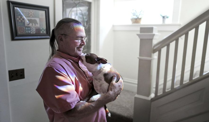 Billy Bob Grahn, founder and director of the Red Road House, holds Miss Ella near the staircase of their home in Janesville, Wis., on Wednesday, Sept. 13, 2017.  (Anthony Wahl/The Janesville Gazette via AP)