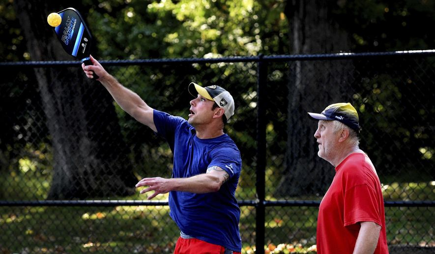 In this Wednesday, Sept. 13, 2017 photo, Kaan Cercioglu, 36, left, an Army veteran who served two tours in Iraq, hits the ball back as teammate Kirk Juffer, 64, looks on during a pickleball game at Shawnee Park in Woodbury, Minn. Woodbury recently tore out two unused tennis courts in Shawnee Park and replaced them with six pickleball courts. Officials were flabbergasted to see how popular those courts have become.  (Jean Pieri/Pioneer Press via AP)