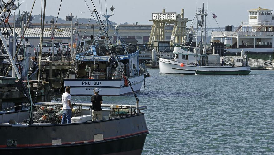 File - In this Nov. 5, 2015 file photo, fishermen stand on a boat at Fisherman's Wharf in San Francisco. Fish is returning to San Francisco's Fisherman's Wharf. Starting this weekend, San Francisco will allow fishermen to sell their dabs, sole and rockfish at the popular tourist spot as part of a one-year pilot program. (AP Photo/Ben Margot, File)