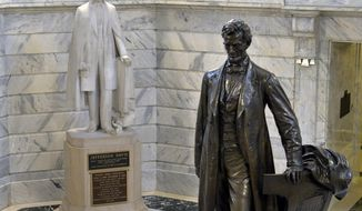 """FILE - In this Aug. 5, 2015 file photo, a statue of Jefferson Davis, left, faces a statue of Abraham Lincoln in the Rotunda of the state Capitol in Frankfort, Ky.   A panel of historic properties advisers in Kentucky on Thursday, Sept. 21, 2017, has recommended removing a plaque from the statue of Jefferson Davis that identifies the only president of the Confederacy as a """"patriot, hero, statesman."""" (AP Photo/Timothy D. Easley, File)"""