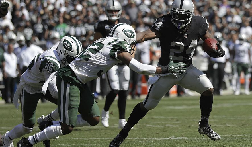 Oakland Raiders running back Marshawn Lynch (24) runs against New York Jets cornerback Juston Burris (32) during the first half of an NFL football game in Oakland, Calif., Sunday, Sept. 17, 2017. (AP Photo/Marcio Jose Sanchez)