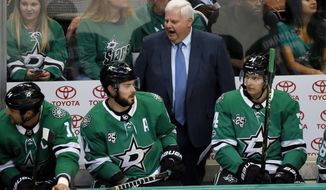 FILE - In this Tuesday, Sept. 19, 2017, file photo, Dallas Stars head coach Ken Hitchcock, center, gives instructions to the bench as Jamie Benn (14), Tyler Seguin (91) and Denis Gurianov (34) listen in the first period of a preseason NHL hockey game against the St. Louis Blues in Dallas. The Stars may have led the league in significant moves during their long offseason, putting Hitchcock behind their bench again and players such as Ben Bishop and Alexander Radulov on the ice. (AP Photo/Tony Gutierrez, File)