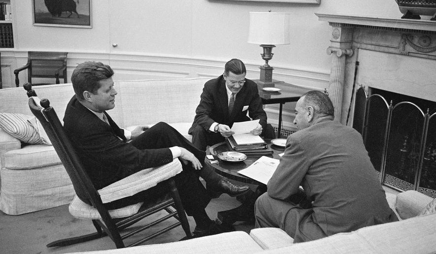 FILE - In this March 16, 1961 file photo, President John F. Kennedy sits in his favorite rocking chair in his office during a meeting with Secretary of Defense Robert McNamara and Vice President Lyndon B. Johnson, right, at the White House in Washington. A replica of the rocking chair commissioned and gifted by Kennedy is up for sale at a Los Angeles auction that will take place on Nov. 17, 2017. (AP Photo/Henry Burroughs, File)