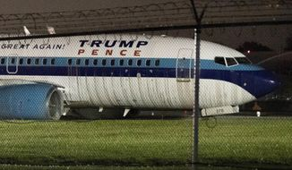 FILE- In this Oct. 27, 2016 file photo, Republican vice presidential candidate, Indiana Gov. Mike Pence's campaign airplane sits partially on the tarmac and the grass after sliding off the runway while landing at LaGuardia airport in New York. A report by the National Transportation Safety Board released on Thursday, Sept. 21, 2017, held the pilots responsible for the aircraft over-running the runway. (AP Photo/Mary Altaffer, File)
