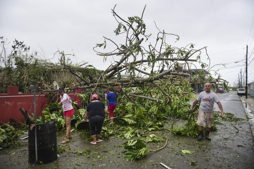 A family helps clean the road after Hurricane Maria hit the eastern region of the island, in Humacao, Puerto Rico, Tuesday, September 20, 2017. The strongest hurricane to hit Puerto Rico in more than 80 years destroyed hundreds of homes, knocked out power across the entire island and turned some streets into raging rivers in an onslaught that could plunge the U.S. territory deeper into financial crisis. (AP Photo/Carlos Giusti)