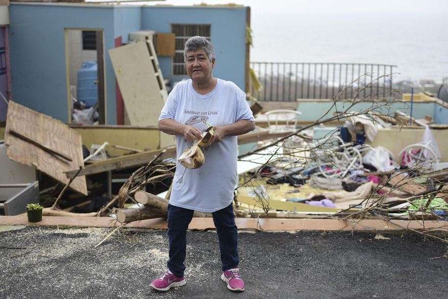"""Whats important is ones life"" says Rufina Fernandez standing in front of her daughters ruined house while eating a coconut a day after the impact of Hurricane Maria, in Yabucoa, Puerto Rico, Thursday, September 21, 2017. As of Thursday evening, Maria was moving off the northern coast of the Dominican Republic with winds of 120 mph (195 kph). The storm was expected to approach the Turks and Caicos Islands and the Bahamas late Thursday and early Friday. (AP Photo/Carlos Giusti)"