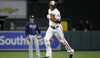 Baltimore Orioles' Manny Machado rounds the bases past Tampa Bay Rays shortstop Daniel Robertson after hitting a two-run home run in the first inning of a baseball game in Baltimore, Thursday, Sept. 21, 2017. (AP Photo/Patrick Semansky)