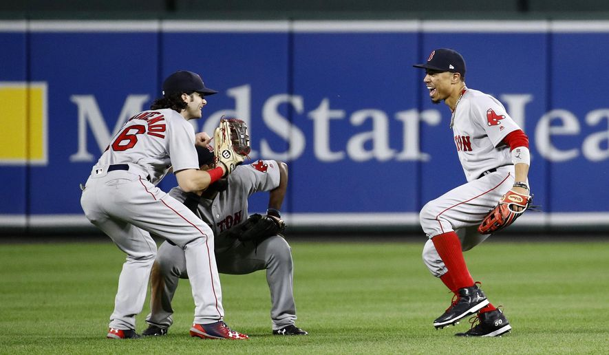 Boston Red Sox outfielders Andrew Benintendi, from left, Jackie Bradley Jr. and Mookie Betts celebrate after a baseball game against the Baltimore Orioles in Baltimore, Wednesday, Sept. 20, 2017. Boston won 9-0. (AP Photo/Patrick Semansky)