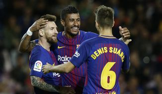 FC Barcelona's Lionel Messi, left, celebrates after scoring with his teammate Paulinho, center, and Denis Suarez during the Spanish La Liga soccer match between FC Barcelona and Eibar at the Camp Nou stadium in Barcelona, Spain, Tuesday, Sept. 19, 2017. (AP Photo/Manu Fernandez)