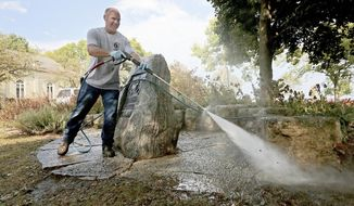 Cal Steinberg of the City of Madison, Wis. Facilities and Maintenance Department cleans the area around a memorial at the Gates of Heaven Synagogue building after using a high pressure hose and 248-degree water to remove anti-Semitic graffiti from the stone marker outside the historic building in the city Wednesday, Sept. 20, 2017. (John Hart/Wisconsin State Journal via AP)