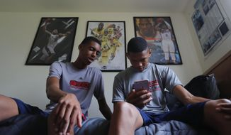 Emoni Bates, left, talks with Ty Rodgers in his room in Superior Township, Mich., July 21, 2017.  Bates is the best 13-year-old basketball player in America, according to some recruiting services. One of his highlight reels on YouTube has been viewed about 1 million times. (AP Photo/Paul Sancya)
