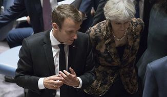 French President Emmanuel Macron speaks to British Prime Minister Theresa May as they leave a high level Security Council meeting on United Nations peacekeeping operations, Wednesday, Sept. 20, 2017 at U.N. headquarters. (AP Photo/Mary Altaffer)