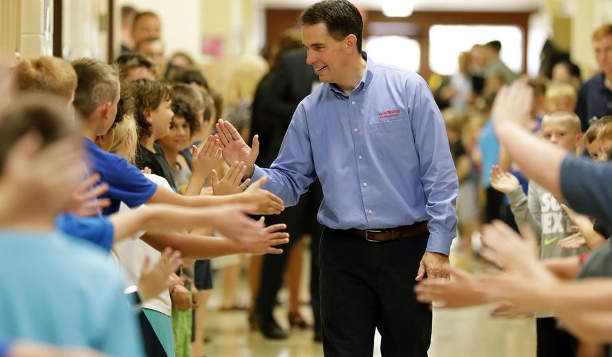 Governor Scott Walker high-fives students after signing the 2017-2019 state budget bill into law Thursday,  Sept. 21, 2017, at Tullar Elementary School in Neenah, Wis. (Dan Powers/The Post-Crescent via AP)