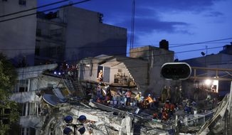 Rescuers race to save people believed to be still alive inside a collapsed office building in the Roma Norte neighborhood of Mexico City, as night falls Friday, Sept. 22, 2017, three days after a 7.1 magnitude earthquake. (AP Photo/Rebecca Blackwell)