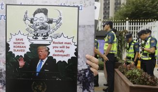 "A North Korean defector holds a banner as police officers stand guard during a rally against South Korean government's policy against the North in front of the Government Complex in Seoul, South Korea, Friday, Sept. 22, 2017. North Korean leader Kim Jong Un, in an extraordinary and direct rebuke, called U.S. President Donald Trump ""deranged"" and said he will ""pay dearly"" for his threats, a possible indication of more powerful weapons tests on the horizon. (AP Photo/Ahn Young-joon)"
