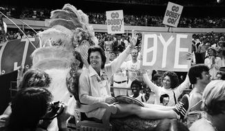 FILE - In this Sept. 20, 1973, file photo, . Billie Jean King waves to crowds at the Astrodome in Houston, Texas, as she is borne onto the crowd on a multi-colored throne carried by four men for her match with Bobby Riggs.(AP Photo/File)