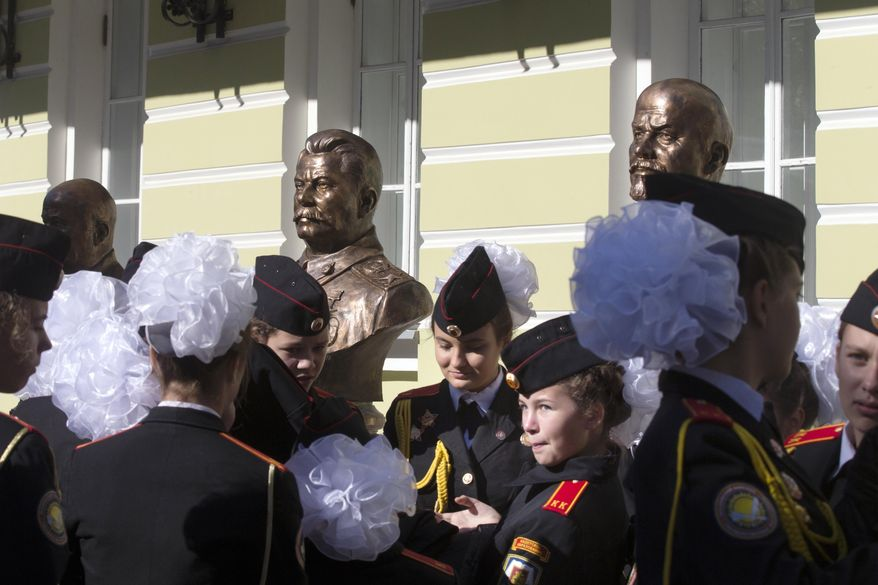 "Students of a military-sponsored school attend the opening of a series of Russian leaders, including Vladimir Lenin, background right, and Josef Stalin, background center, in Moscow, Russia, Friday, Sept. 22, 2017. The Russian Military-Historic Society, an organization founded by President Vladimir Putin and led by his culture minister, unveiled the sculptures Friday to expand its ""alley of rulers"" at a Moscow park, which until now had featured busts of Russian monarchs. It described the new display as part of efforts to preserve Russian history. (AP Photo/Alexander Zemlianichenko)"