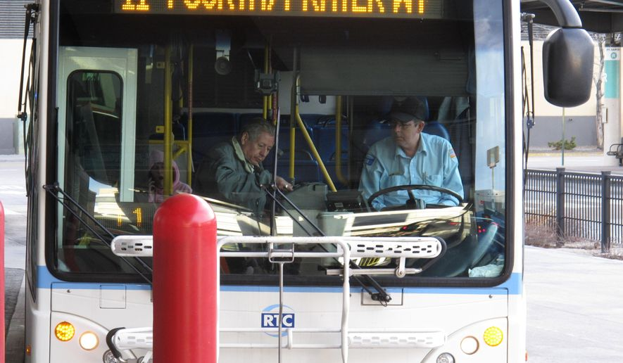 FILE - In this March 2, 2016 file photo, a passenger boards a city bus while the driver looks on at the bus station in downtown Reno, Nev. A federal judge has given northern Nevada's largest public transit system the green light to begin recording audio along with video surveillance on city buses despite objections from the bus drivers' union that it's an illegal invasion of privacy. U.S. District Judge Miranda Du said in a ruling this week neither the drivers nor their passengers have a right to privacy because conversations on public buses are not private. (AP Photo/Scott Sonner, File)