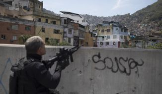 A police officer takes a position during an operation in the Rocinha slum in Rio de Janeiro, Brazil, Friday, Sept. 22, 2017. Shootouts have erupted in several areas of Rio de Janeiro, prompting Brazilian authorities to shut roads and close schools. (AP Photo/Leo Correa)