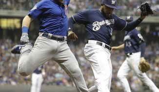 Chicago Cubs' Ian Happ is safe at first as he beats Milwaukee Brewers' Jeremy Jeffress to the bag during the ninth inning of a baseball game Thursday, Sept. 21, 2017, in Milwaukee. (AP Photo/Morry Gash)