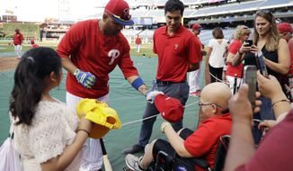 In this Wednesday, Sept. 20, 2017 photo, Philadelphia Phillies' team translator Diego Ettedgui, center, watches as Andres Blanco, left, meets with fans before a baseball game against the Los Angeles Dodgers, in Philadelphia. (AP Photo/Matt Slocum)