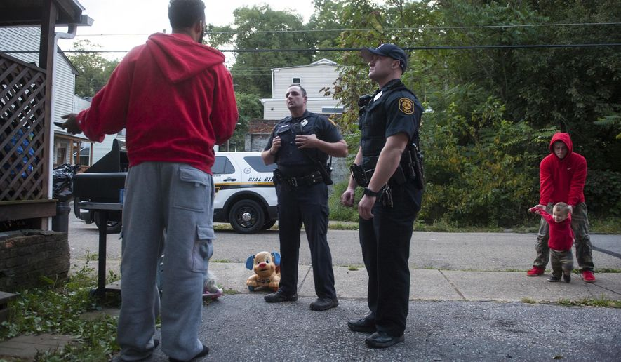 """ADVANCE FOR SATURDAY SEPT. 23 AND THEREAFTER - In a Tuesday, Sept. 12, 2017 photo, Pittsburgh Police Neighborhood Resource Officer Eric Defeo, center left, and fellow Zone 1 Officer Joseph Opferman, center right, respond to a call about a domestic disagreement in Marshall-Shadeland. """"There's one aspect of this job that I've always liked, and it's more of my personality, and that job is talking with people,"""" said Defeo, now in the position since mid-August. Defeo got the man's cellphone number to follow up with him later in the night. (Stephanie Strasburg/Pittsburgh Post-Gazette via AP)"""